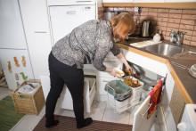 Nainen kaataa biojätettä biojäteastiaan a woman putting biowaste to a biowaste bin