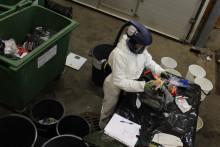 Henkilö tutkii sekajätettä kokeilutaloyhtiön jätehuoneessa.